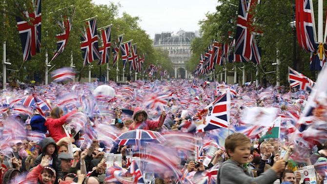 "FILE - In this June 5, 2012 file photo revelers on the Mall in London watch Britain Queen Elizabeth II appear on the Buckingham Palace balcony as part of a four-day Diamond Jubilee celebration to mark the 60th anniversary of  Queen Elizabeth II accession to the throne. The British government is revising the ""Life in the U.K."" handbook and test taken by those seeking to settle in Britain. While the previous version contained some practical questions about daily life, the emphasis is now on British history and culture. There are questions on sports, music and historical figures from William Shakespeare to Winston Churchill. The government says the new handbook, published Monday Jan. 28, 2012, also features ""an exploration of Britons' unique sense of humor and satire."" (AP Photo/Sang Tan, File)"
