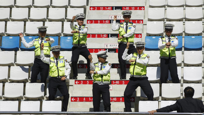 """Policemen rehearse South Korean singer Psy's """"Gangnam style"""" dance moves at the grandstand ahead of the South Korean F1 Grand Prix in Yeongam"""