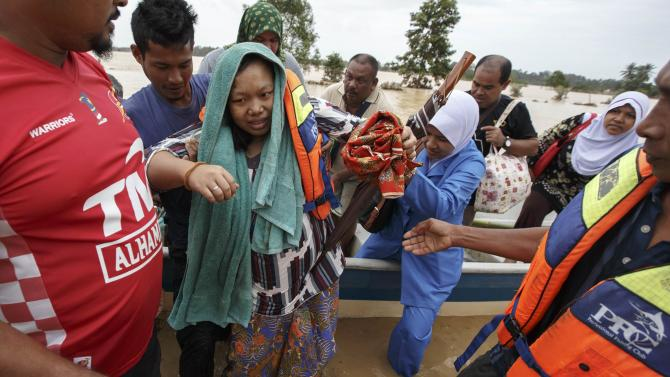 A pregnant woman is evacuated from her home by rescue workers as she is taken to a hospital, on the outskirts of Kota Bharu