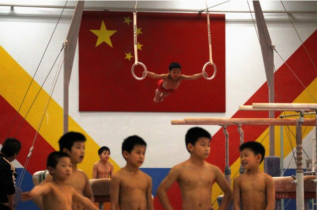 File photo of young gymnasts standing together as a classmate hangs from gymnastic rings in front of a Chinese national flag during a gymnastics class at the Shichahai Sports School in Beijing