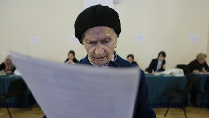 An elderly voter looks at her ballot at a polling station during parliamentary elections in Kiev, Ukraine, Sunday, Oct. 26, 2014. Voters in Ukraine headed to the polls Sunday to elect a new parliament, overhauling a legislature tainted by its association with ousted President Viktor Yanukovych. (AP Photo/Sergei Chuzavkov)