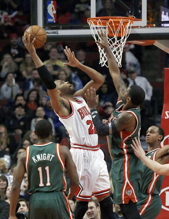 Chicago Bulls forward Taj Gibson (22) shoots over Milwaukee Bucks shooting guard O.J. Mayo, right, as Brandon Knight (11) watches during the first half of an NBA basketball game Tuesday, Dec. 10, 2013