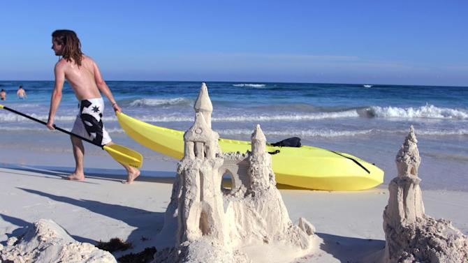 In this Jan. 3, 2013 photograph, a man drags a kayak past a sand castle in Tulum, Mexico. Despite its proximity to Cancun and its fellow party neighbor Playa del Carmen, Tulum is not for the same spring break crowd, attracting a mix of bohemians, well-pocketed New Age types and sun-seekers to its turquoise waters and white sandy beaches. (AP Photos/Manuel Valdes)