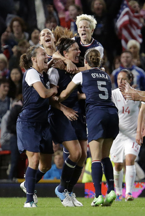 United States' Abby Wambach, center, celebrates her penalty goal with her teammates during the semi final women's soccer match between the USA and Canada at the 2012 London Summer Olympics, in Manches