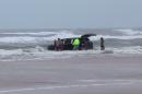 In this image made from video, lifeguards and bystanders rescue children from a minivan that their mother, 31-year-old Ebony Wilkerson, drove into the Atlantic, Tuesday, March 4, 2014 in Daytona Beach, Fla. The pregnant South Carolina woman who drove the minivan carrying her three young children into the ocean surf had talked about demons before leaving the house, according to her sister who worriedly called police, officials said during a news conference Wednesday. (AP Photo/Simon Besner) NO SALES