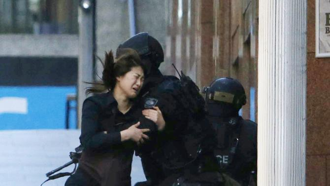 File photo of a hostage running towards a police officer outside Lindt cafe in Sydney