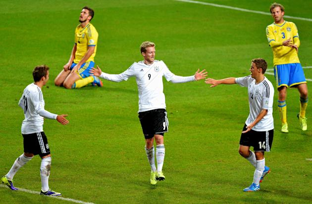 Germany's Andre Schuerrle, center, celebrates scoring with teammates Mario Goetze, left, and Max Kruse while Sweden's Per Nilsson, far left, and Mikael Antonsson look dejected during the 2014 World Cu
