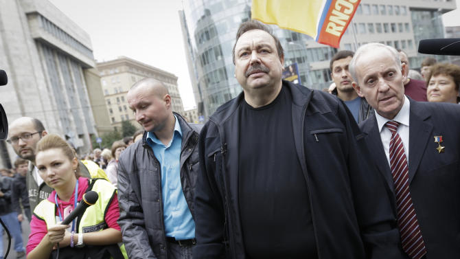 Opposition activist Gennady Gudkov, center, walks with opposition supporters during a protest demonstration in Moscow, Saturday, Sept. 15, 2012. Thousands of protesters marched across downtown Moscow on Saturday in the first major rally in three months against President Vladimir Putin, while defying the Kremlin's ongoing efforts to crackdown on opposition. Gennady Gudkov was stripped of his parliament seat by the Kremlin-controlled parliament on Friday. (AP Photo/Sergey Ponomarev)