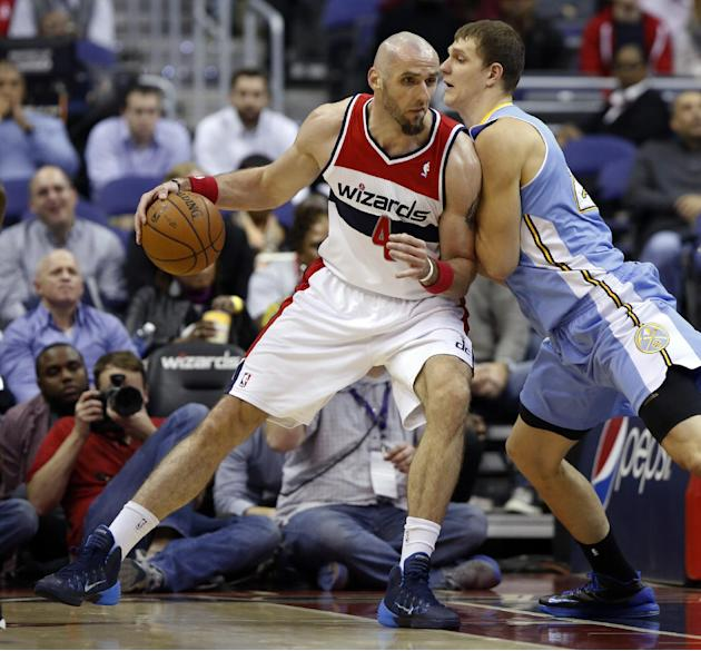 Washington Wizards center Marcin Gortat (4), from Poland, drives against Denver Nuggets center Timofey Mozgov, right, from Russia, in the first half of an NBA basketball game on Monday, Dec. 9, 2013,