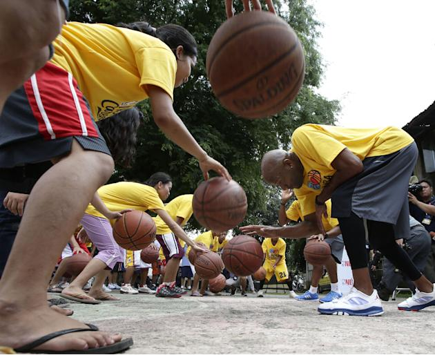 Former NBA basketball player Ron Harper conducts basketball clinic before the less-privileged children at the Boys Town Rehabilitation Center at suburban Marikina city east of Manila Sunday Oct. 6, 20