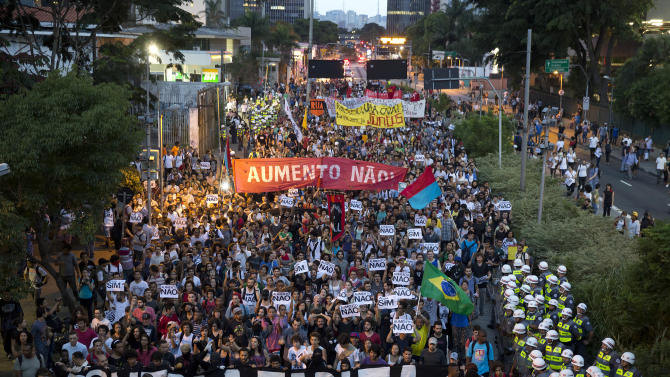 "Demonstrators march holding banners that read in Portuguese ""Against the Fare,"" and ""No Rise,"" during a protest against the price hike on public transportation in Sao Paulo, Brazil, Tuesday, Jan. 27, 2015. The price to ride the subway and bus in Sao Paulo increased from 3 Brazilian Reals ($1.16) to 3.50 Brazilian Reals ($1.36). (AP Photo/Andre Penner)"