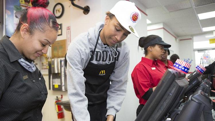 IMAGE DISTRIBUTED FOR MCDONALD'S - McDonald's All American Games player Oderah Chidom, center, is seen at the cash register during a send-off event  at a McDonald's restaurant on Wednesday March 20, 2013, in Oakland, Calif. The celebration is being held prior to the All American Games in Chicago on April 3rd. Three student athletes from the Bay Area were selected among 800 nominees to participate in McDonald's All American Games. The elite list of prep school stand outs has included Michael Jordan, Kobe Bryant and LeBron James. (Photo by Annie Tritt/Invision for McDonald's/AP Images)