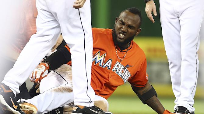 Miami Marlins runner Marcell Ozuna reactss after he hurt his leg during the seventh inning of a baseball game against the Washington Nationals in Miami, Sunday, Sept. 21, 2014.  The Nationals won 2-1. (AP Photo/J Pat Carter)