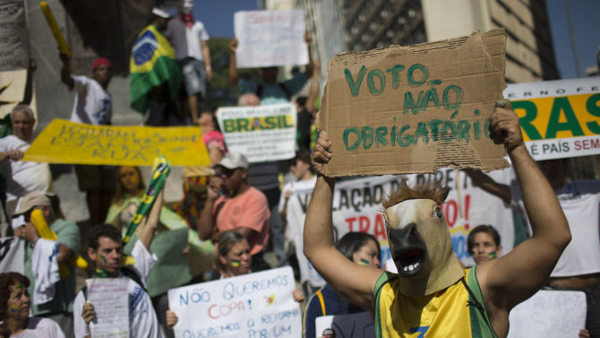 "A masked demonstrator holds up a sign that reads in Portuguese ""No mandatory vote,"" referring to Brazil's law that citizens are obligated to vote in all elections, during a protest march toward the Mineirao stadium where a Confederations Cup semifinal soccer match will be played between Brazil and Uruguay in Belo Horizonte, Brazil, Wednesday, June 26, 2013. The wave of protests that hit Brazil on June 17 began as opposition to transportation fare hikes, then expanded to a list of causes including anger at high taxes, poor services and high World Cup spending, before coalescing around the issue of rampant government corruption. (AP Photo/Felipe Dana)"