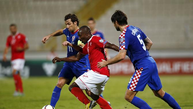 Malta's Effiong tries to pass through Croatia's Srna and  Corluka during their Euro 2016 Group H qualification soccer match at the National Stadium in Ta' Qali, outside Valletta