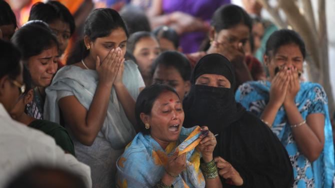 Relatives and neighbors mourn by the body of Swapna Reddy, killed in Thursday's explosion, at their house in Hyderabad, India, Friday, Feb. 22, 2013. A day after two bicycle bombs killed more than a dozen people and wounded more than 100, investigators into India's worst bombing in more than a year searched Friday for possible links to anger over the execution of a Muslim militant. (AP Photo/ Mahesh Kumar A.)