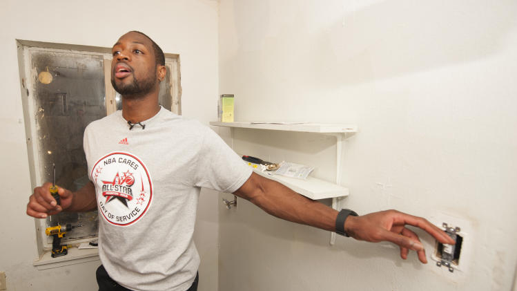 IMAGE DISTRIBUTED FOR REBUILDING TOGETHER - Miami Heat's Dwayne Wade checks a light switch during the Rebuild Together NBA Cares All-Star Day of Service project, Friday, Feb. 15, 2013, in Houston. Hundreds of volunteers painted, landscaped, and did other repairs to five homes in the neighborhood. (Dave Einsel/AP Images for Rebuilding Together)