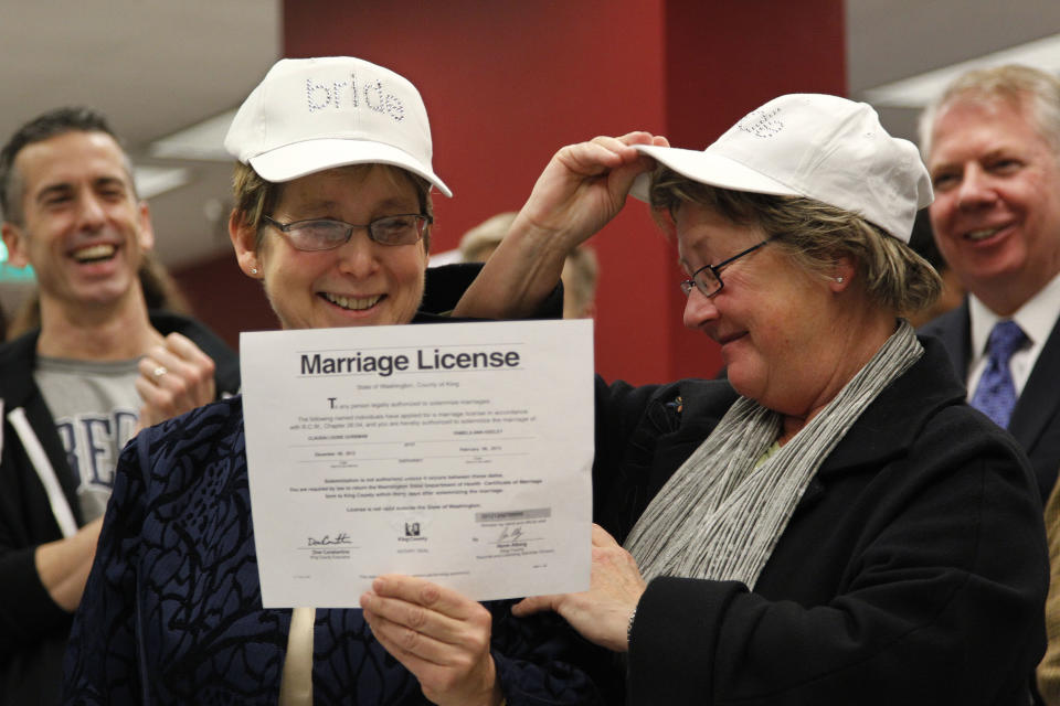 "Claudia Gorbman, left, and partner Pam Keeley wear caps both reading ""bride"" as they display their newly-issued marriage license, Thursday, Dec. 6, 2012, in Seattle. King County Executive Dow Constantine  began issuing the licenses immediately upon certification of the November election that passed Referendum 74. (AP Photo/Elaine Thompson)"