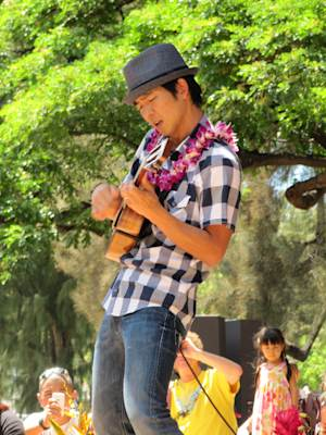 Ukulele musician Jake Shimabukuro is seen playing the instrument at the 41st Annual Ukulele Festival in Honolulu Sunday July 17, 2011. Organizers estimate 10,000 people came to Kapiolani Park for the festival this year.(AP Photo/Audrey McAvoy)