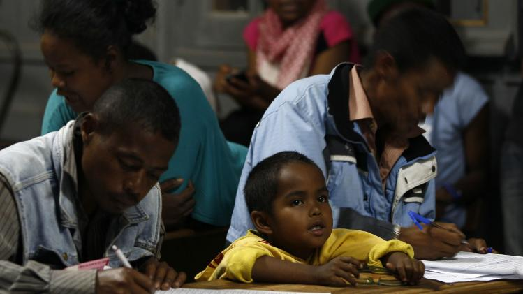 A boy sits between polling agents as they tally counted votes at a polling centre in Madagascar's capital Antananarivo