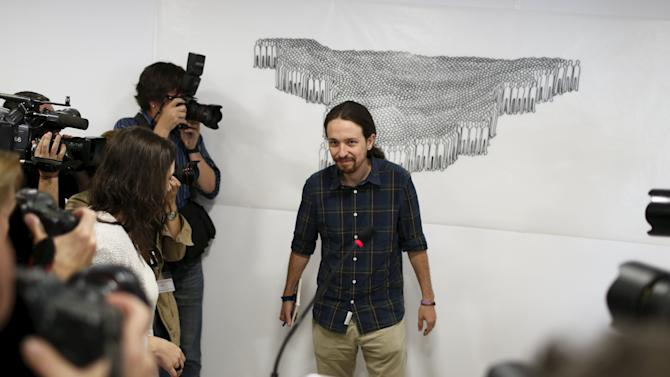 Pablo Iglesias, leader of the Podemos (We Can) party, is surrounded by photographers at the start of a news conference in Madrid
