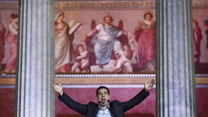 """Leader of Syriza left-wing party Alexis Tsipras speaks to his supporters outside Athens University Headquarters, Sunday, Jan. 25, 2015. A triumphant Alexis Tsipras told Greeks that his radical left Syriza party's win in Sunday's early general election meant an end to austerity and humiliation and that the country's regular and often fraught debt inspections were a thing of the past. """"Today the Greek people have made history. Hope has made history,"""" Tsipras said in his victory speech at a conference hall in central Athens. (AP Photo/Petros Giannakouris)"""