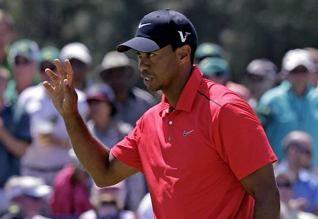 Tiger Woods waves after his putt on the ninth green during the fourth round of the Masters golf tournament Sunday, April 8, 2012, in Augusta, Ga. (AP Photo/Darron Cummings)