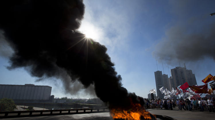 Workers burn tires to block a bridge that leads to the capital during a 24-hour general strike in Buenos Aires, Argentina, Tuesday, Nov. 20, 2012.  Argentine President Cristina Fernandez is facing a nationwide strike, led by union bosses who once were her most steadfast supporters. Many trains and bus lines are paralyzed; banks, courts and schools are closed; airlines have canceled flights and small groups of people have blocked highways in about a dozen places around the capital. (AP Photo/Victor R. Caivano)