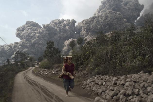 A villager runs as Mount Sinabung erupt at Sigarang-Garang village in Karo district