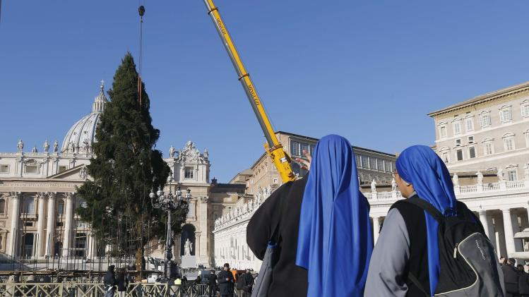 Nuns looks as workers erect Christmas tree, more than 20 metres high, in St. Peter's Square at the Vatican