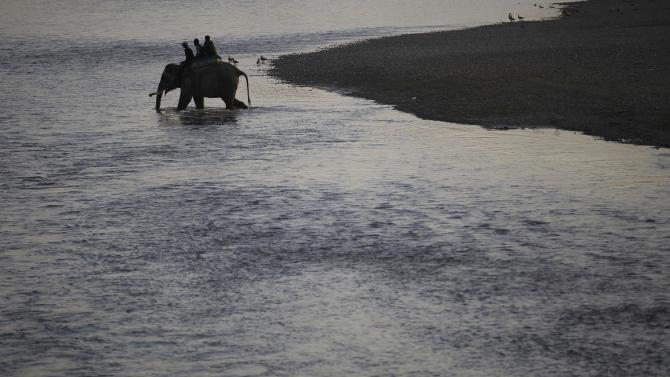 People ride on an elephant as they cross the Rapti River while returning from the Elephant Festival event at Sauraha in Chitwan