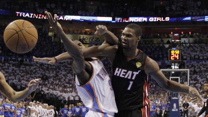 Oklahoma City Thunder power forward Serge Ibaka (9) from Republic of Congo and Miami Heat power forward Chris Bosh go after a rebound during the first half at Game 2 of the NBA finals basketball series, Thursday, June 14, 2012, in Oklahoma City. (AP Photo/Jeff Roberson, Pool)