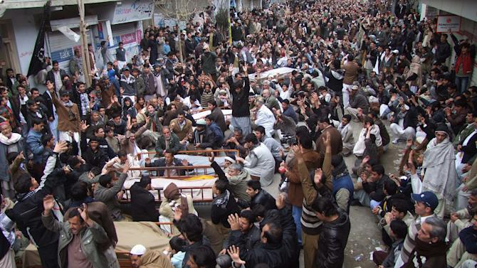 Pakistani Shiite Muslims chant slogans next to the bodies of their relatives awaiting burial, who were killed in Thursday's deadly bombings, at a protest rally, Friday, Jan. 11, 2013 in Quetta, Pakistan. Shiites in a southwestern Pakistani city hit by a brutal terror attack refused to bury their dead Friday in protest, demanding that the government do something to protect them from what has become a barrage of bombings and shootings against the minority Muslim sect. (AP Photo/Arshad Butt)