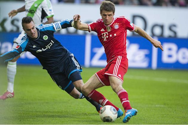 Bayern's Thomas Mueller, right, scores his side's 2nd goal against Wolfsburg goalkeeper Diego Benaglio of Switzerland during the German Bundesliga soccer match between VfL Wolfsburg and Bayern