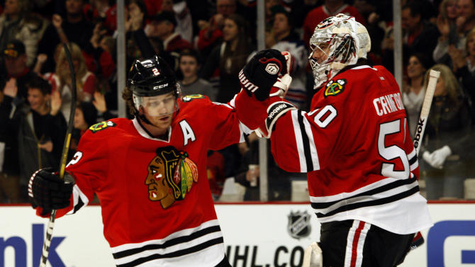 Chicago Blackhawks' Duncan Keith, left, is congratulated by Blackhawks goalie Corey Crawford in the first period after Keith scored against the Detroit Red Wings during an NHL hockey game in Chicago, Sunday, Jan. 27, 2013. (AP Photo/John Smierciak)