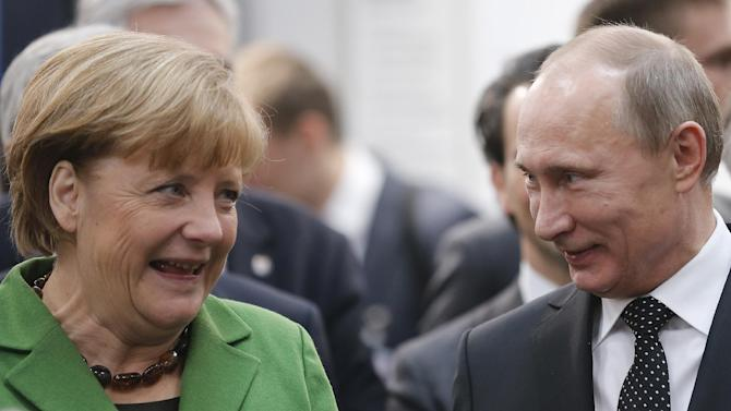 Russian President Vladimir Putin and German Chancellor Angela Merkel chat during the opening of the  Hannover Fair in Hannover, Germany, Monday, April 8, 2013.(AP Photo/Frank Augstein)