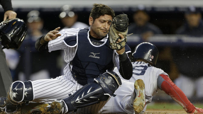 New York Yankees catcher Francisco Cervelli, left, reacts after tagging out Boston Red Sox Shane Victorino, right, who was trying to score on a wild pitch in the first inning of a baseball game at Yankee Stadium in New York, Thursday, April 4, 2013. (AP Photo/Kathy Willens)