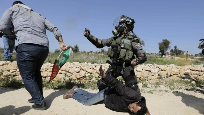 An Israeli border policeman detains a Palestinian protester during clashes at a weekly demonstration against Jewish settlements in the West Bank village of Bilin, near Ramallah