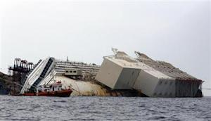"The capsized cruise liner Costa Concordia lies surrounded by containers called ""sponsons"" as part of the salvage plan to remove the wreck of the ship outside Giglio harbour"