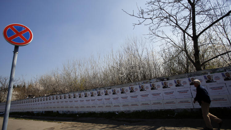"A man walks by posters showing populist leader Aleksandar Vucic with a slogan reading: ""Strongly for reforms"" and ""Strongly against corruption"", in Belgrade, Serbia, Friday, March 14, 2014. Serbian parliamentary elections are scheduled for Sunday, March 16. (AP Photo/Darko Vojinovic)"