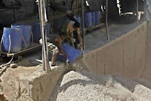 Palestinian workers unload gravel being pulled from …
