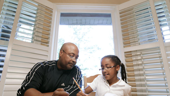 In this April 17, 2012 photo, Roger Witherspoon helps his daughter, Gabrielle, 9, with her homework in Nashville, Tenn. Tennessee is one of only a few states that has passed laws creating evaluations or contracts that put helping with homework or attending teacher conferences into writing. (AP Photo/Mark Humphrey)