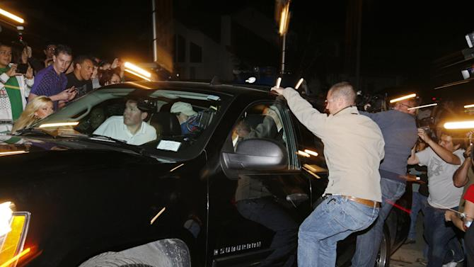 FILE - A March 17, 2009 file photo shows photographers attempting to get photos while hanging onto a moving vehicle carrying octuplets mother Nadya Suleman as she returns to her home in La Habra, Calif.   Suleman has filied for bankruptcy  and her home is scheduled to be auctioned on Monday,  May 7, 2012.  (AP Photo/Jason Redmond, File)