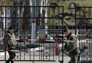 Ukrainian soldiers stand guard at the gate of a military…