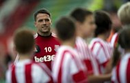 Stoke City's Michael Owen walks over to have a photo taken with team mascots ahead of their English Premier League match against Manchester City at the Brittania Stadium in Stoke, on September 15. Stoke play Chelsea next, at Stamford Bridge in London, on Saturday