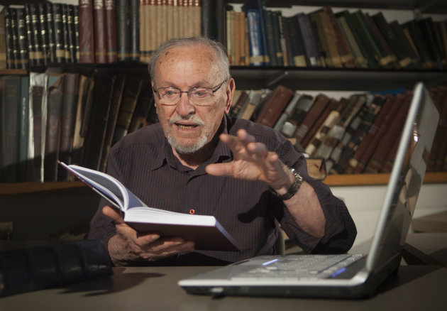 A Tuesday, July 31, 2012 photo, shows biblical scholar Professor Menachem Cohen, reading from a book, at the library of Bar Ilan University, outside Tel Aviv, Israel. For the past 30 years the 84-year-old Judaic biblical scholar has been immersed in a Sisyphean task of correcting all known errors in Jewish scripture to produce a definitive edition of the Hebrew Bible. Now, thanks to the internet, he's bringing it to the general public like never before with a sophisticated search engine that allows even novices to explore the holy text with ease.(AP Photo/Dan Balilty)