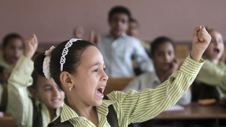 Students raise their hands in class on the first day of their new school year in Giza