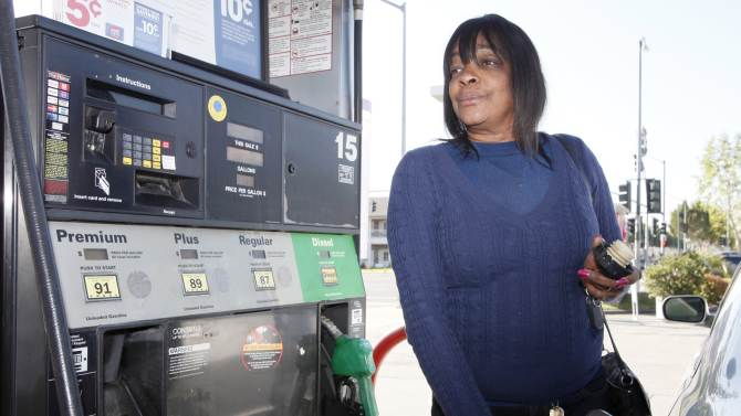 Rosahn Buchanan fills her tank with gas at a station in Arcadia, Calif., Tuesday, March 20,  2012. From all corners of the country, Americans are poorer and angrier these days, thanks to the record fuel prices that have soared above $4 a gallon in some states and could top $5 by summer.(AP Photo/Nick Ut)