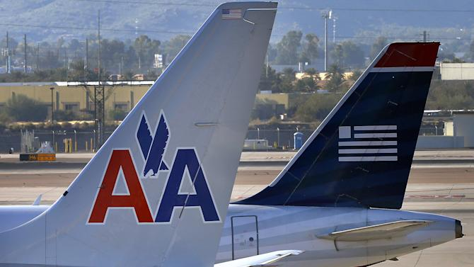 A U.S. Airways jet passes an American Airlines jet, Thursday, Feb. 14, 2013 at Sky Harbor International Airport in Phoenix. The merger of the two airlines has given birth to a mega airline with more passengers than any other in the world. (AP Photo/Matt York)