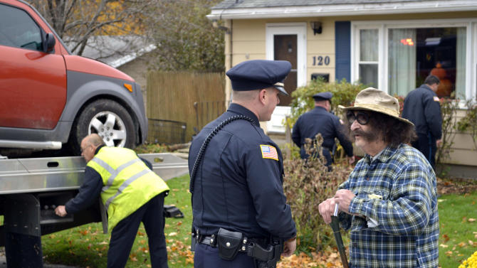 FILE - In this Oct. 24, 2012 file photo, television movie critic Gene Shalit, right, talks with a Lenox, Mass., police officer after crashing his car into a house on Housatonic Street in Lenox. A misdemeanor driving charge against retired television movie critic Gene Shalit is set to be dismissed in Massachusetts. The hearing was continued to April 2, when the driving to endanger charge will be dismissed.  (AP Photo/The Berkshire Eagle, Ben Garver)